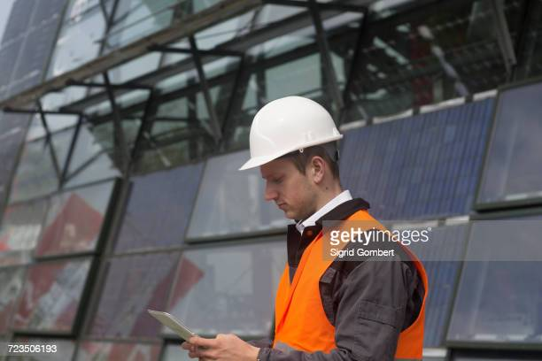 young male engineer looking at digital tablet at solar panel site - sigrid gombert stock pictures, royalty-free photos & images