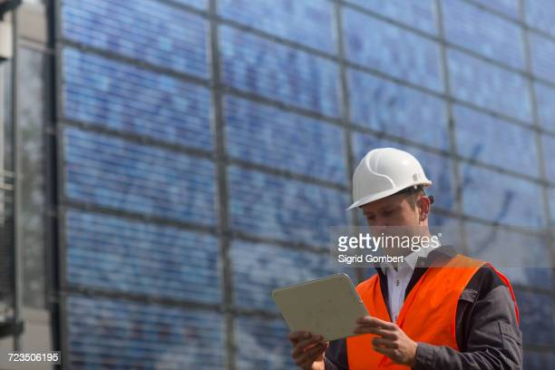 young male engineer looking at digital tablet at solar panel site - sigrid gombert stock-fotos und bilder