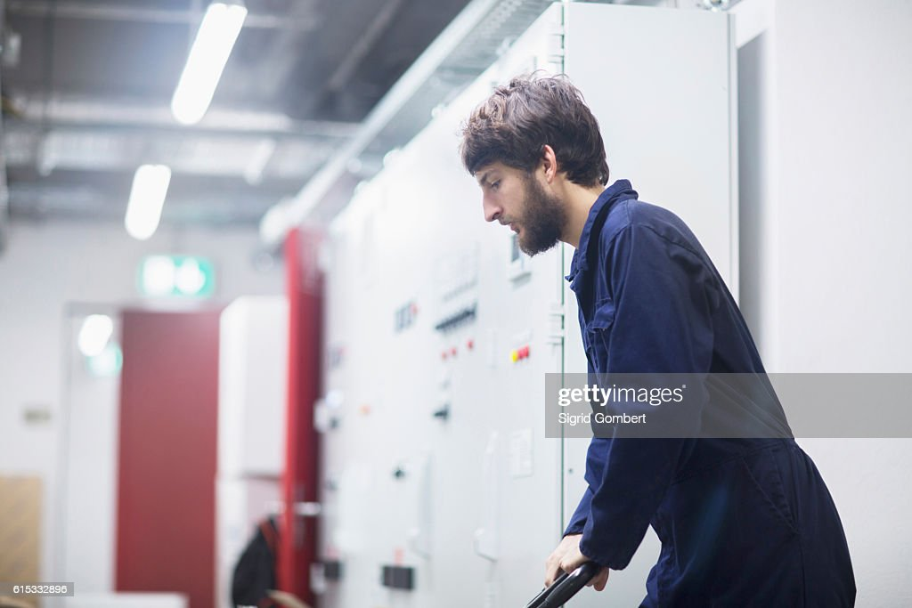 Young male engineer pushing cart in an industrial plant, Freiburg im Breisgau, Baden-Württemberg, Germany : Stock-Foto