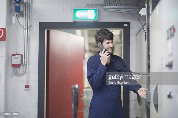 young male engineer talking on landline phone in an industrial plant, freiburg im breisgau, baden-württemberg, germany - sigrid gombert stock pictures, royalty-free photos & images