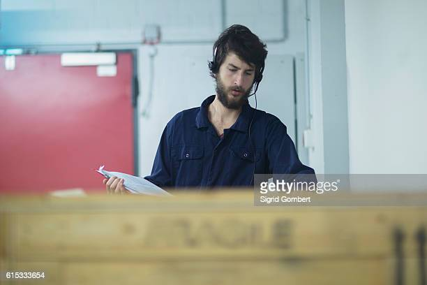 young male engineer wearing headset and checking cargo container in an industrial plant, freiburg im breisgau, baden-württemberg, germany - sigrid gombert stock-fotos und bilder