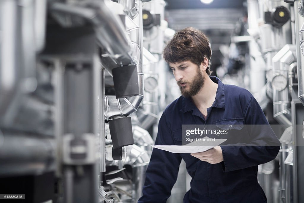 Young male engineer working in an industrial plant, Freiburg im Breisgau, Baden-Württemberg, Germany : Stock-Foto