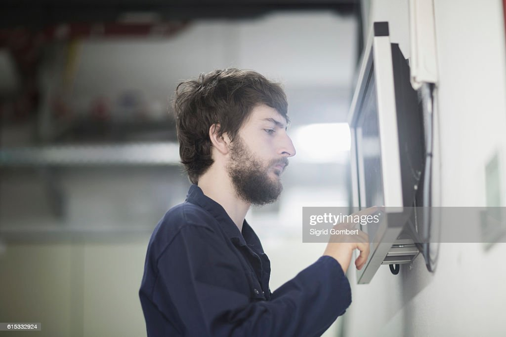 Young male engineer working on touchscreen computer monitor in an industrial plant, Freiburg im Breisgau, Baden-Württemberg, Germany : Stock-Foto