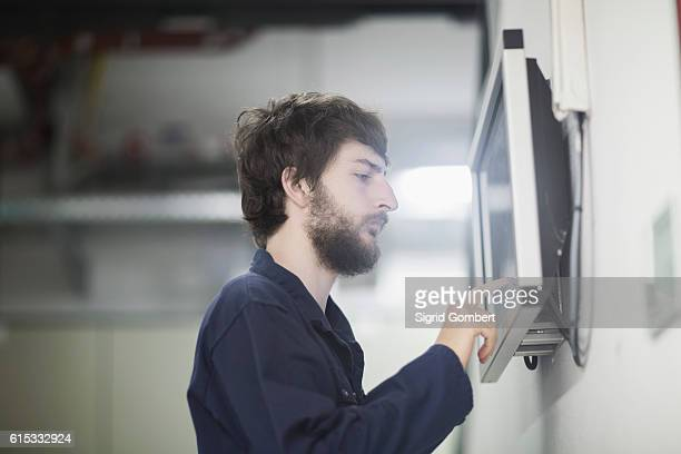 Young male engineer working on touchscreen computer monitor in an industrial plant, Freiburg im Breisgau, Baden-Württemberg, Germany