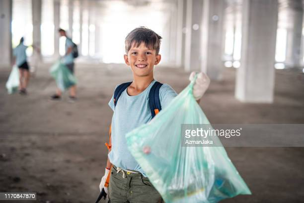 young male environmentalist cleaning up outdoor garage - picking up stock pictures, royalty-free photos & images
