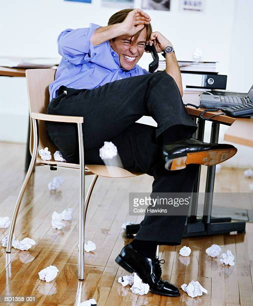 young male executive using telephone, dodging paper balls - ducking stock pictures, royalty-free photos & images