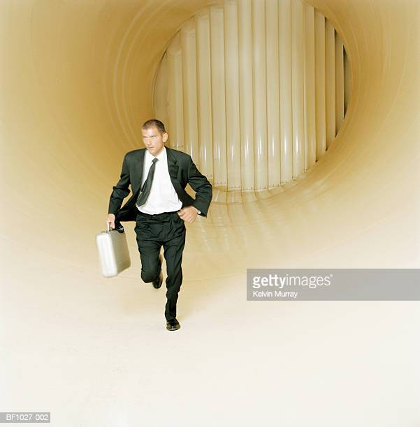 young male executive with briefcase running through wind tunnel - fuggire foto e immagini stock