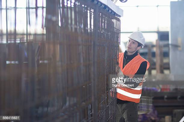 young male factory worker choosing wire mesh in concrete reinforcement factory - sigrid gombert fotografías e imágenes de stock
