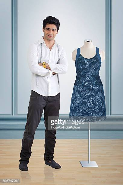 Young male fashion designer standing by mannequin at studio