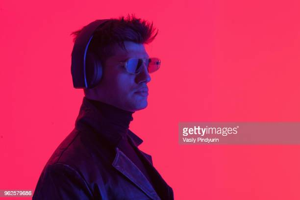 Young male fashion model wearing headphones and sunglasses against coral background