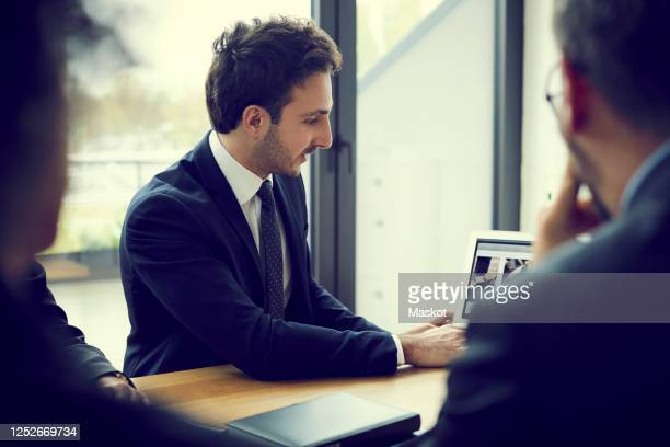 young male financial advisor explaining strategy with laptop during meeting in law firm - 営業職 ストックフォトと画像