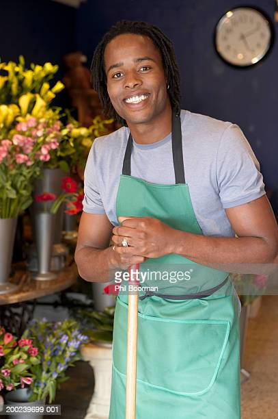Young male florist with broom, smiling, portrait