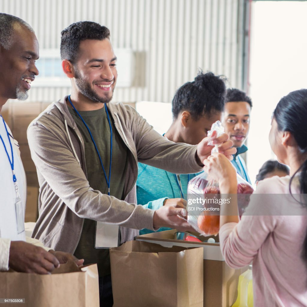 Young male food bank volunteer passes out bags of fruit : Stock Photo