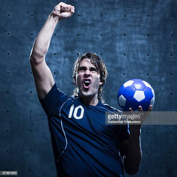 Young male football player punching the air, studio shot