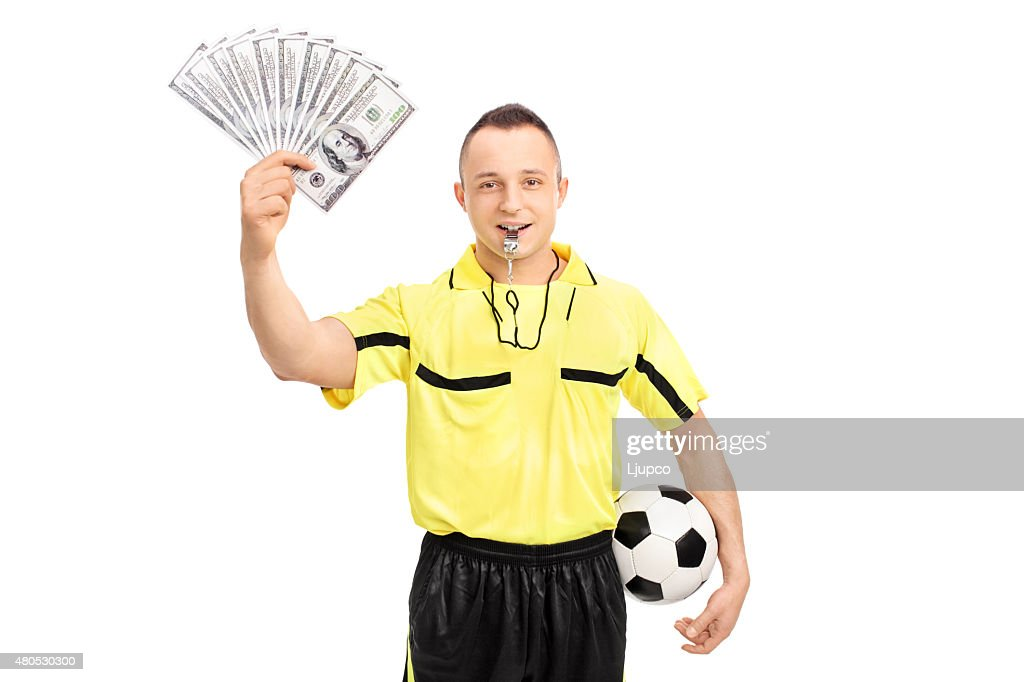 Young male football referee holding a stack of money : Stockfoto