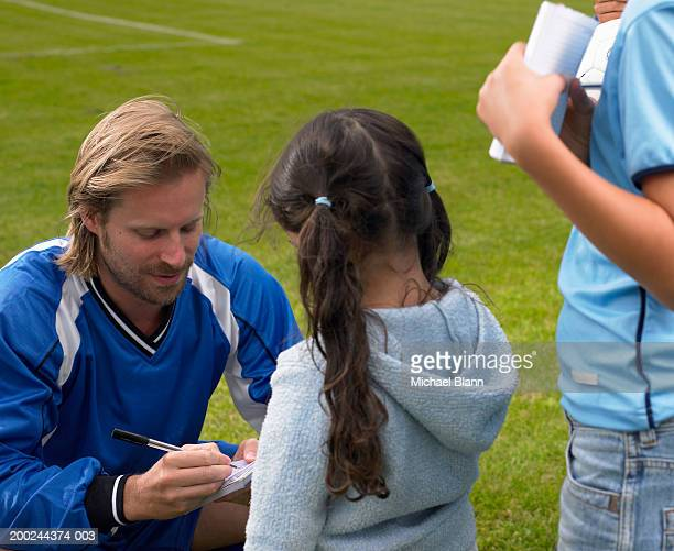 Young male footballer signing autograph for girl (5-7), close-up