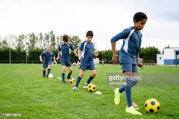 young male footballers doing dribbling drills on field - sports training drill stock pictures, royalty-free photos & images