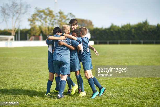 young male footballers in huddled embrace on field - soccer team stock pictures, royalty-free photos & images