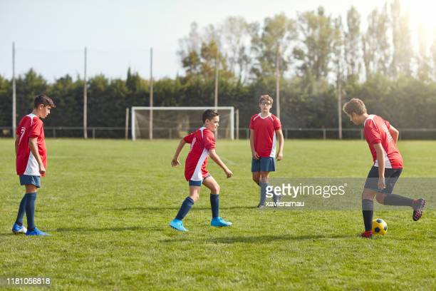 young male footballers in spain practicing passing drills - passing sport stock pictures, royalty-free photos & images