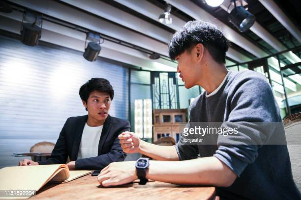 young male friends discuss and celebrate in cafe - ibnjaafar stock photos and pictures