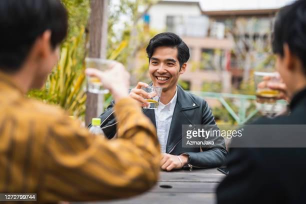 屋外でボトル入りティーを楽しむ若い男性の友人 - 肩越し ストックフォトと画像
