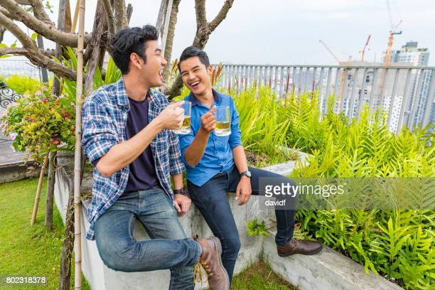 Young Male Friends Having Drinks at a Rooftop Party