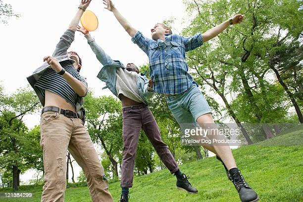Young male friends jumping for a frisbee