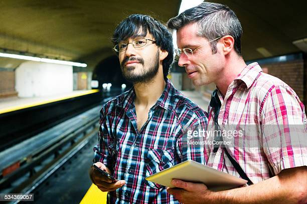 Young male gay couple waiting for subway with phone tablet