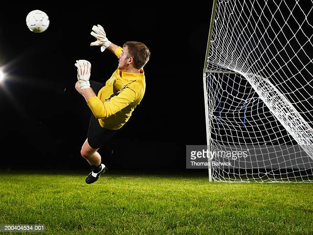 Young male goalie diving for soccer ball, side view