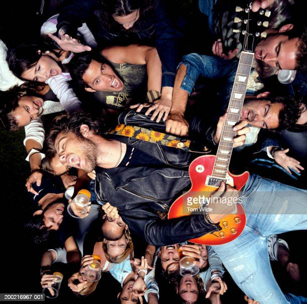 Young male guitarist crowd surfing, portrait