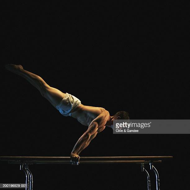 Young male gymnast balancing on parallel bars, side view