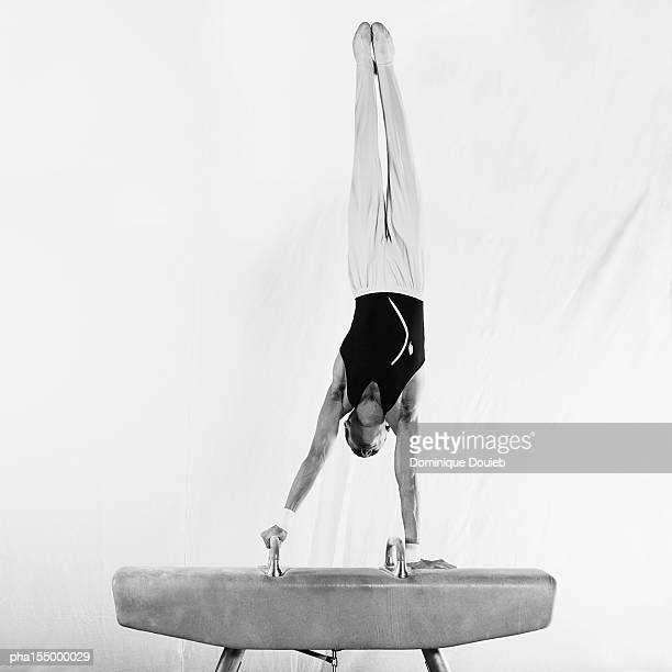 young male gymnast in handstand on pommel horse, b&w. - voltigeerpaard stockfoto's en -beelden