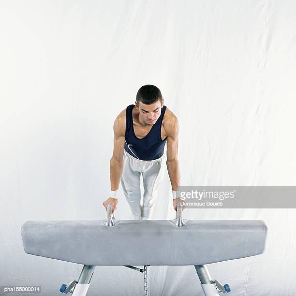 young male gymnast mounting pommel horse. - voltigeerpaard stockfoto's en -beelden