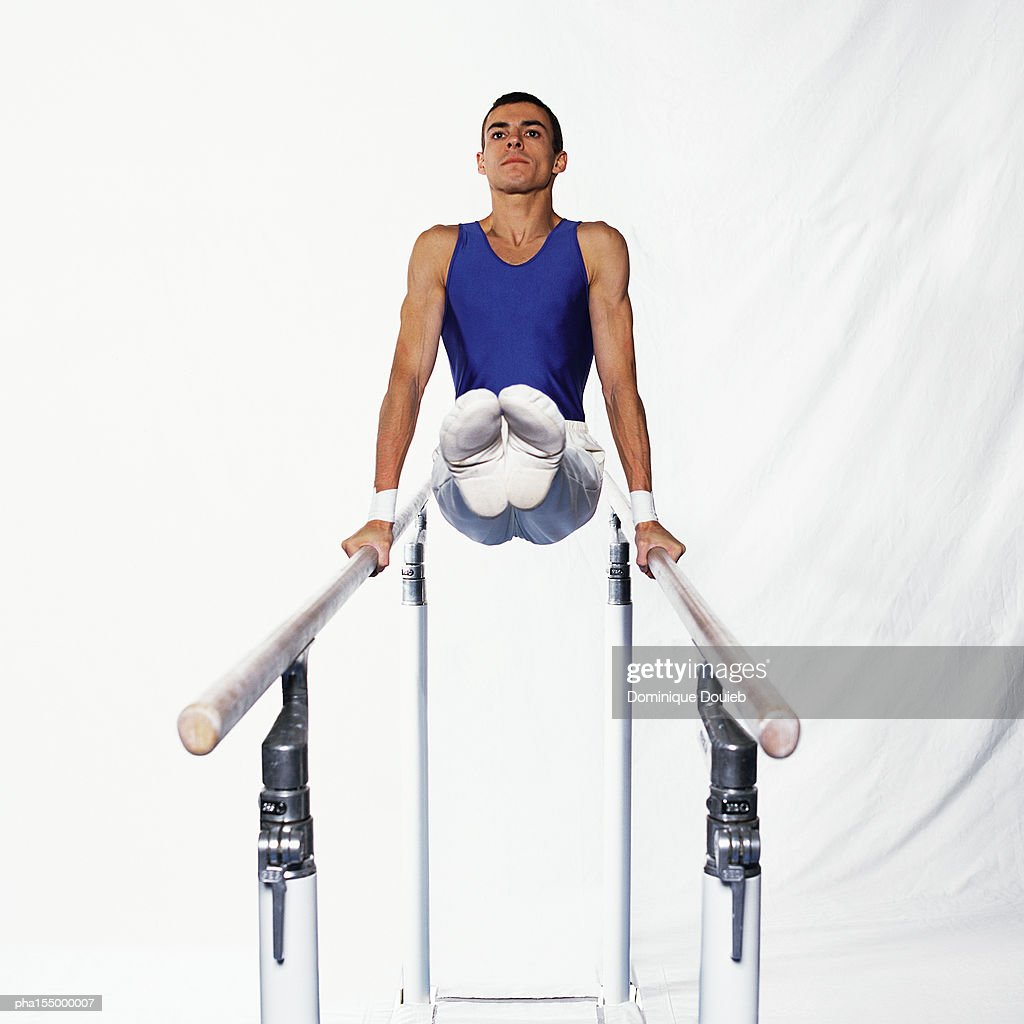 Young male gymnast on parallel bars, side view. : Stockfoto