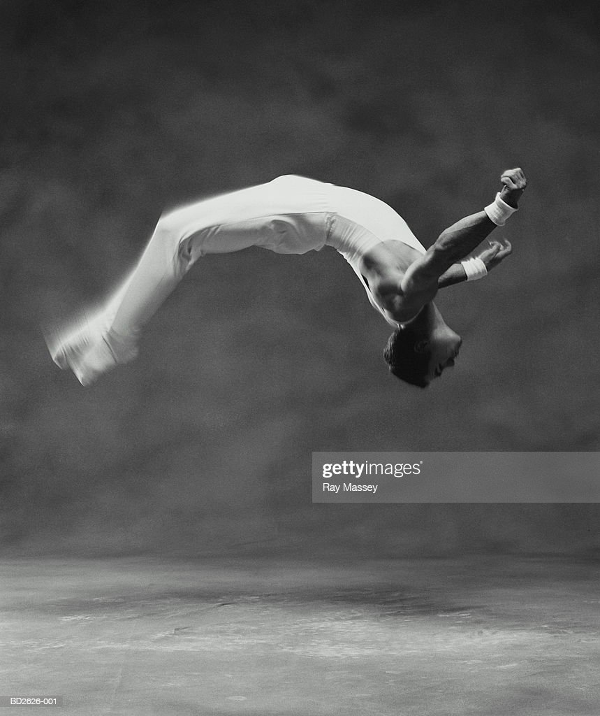 Young male gymnast performing flip (blurred motion, B&W) : Stock Photo