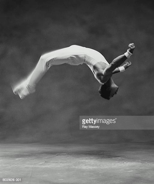 young male gymnast performing flip (blurred motion, b&w) - gymnastics stock pictures, royalty-free photos & images