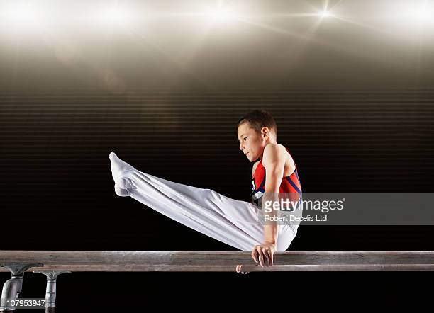 Young male gymnast performing on parallel bars