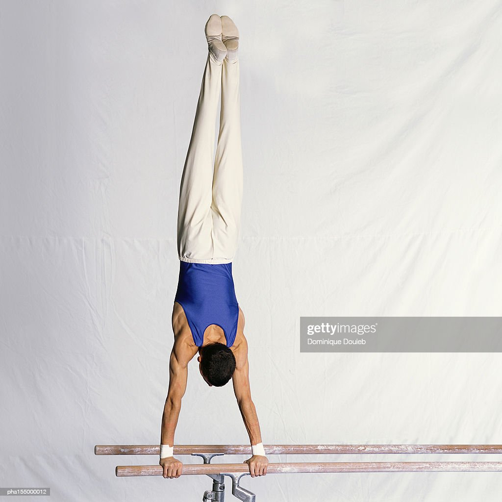 Young male gymnast performing routine on parallel bars, rear view. : Stockfoto