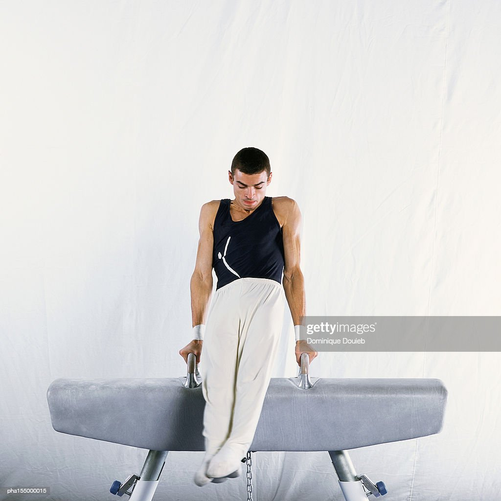 Young male gymnast performing routine on pommel horse. : Stockfoto