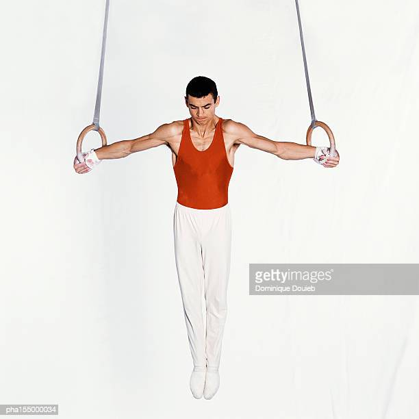 Young male gymnast performing routine on rings.