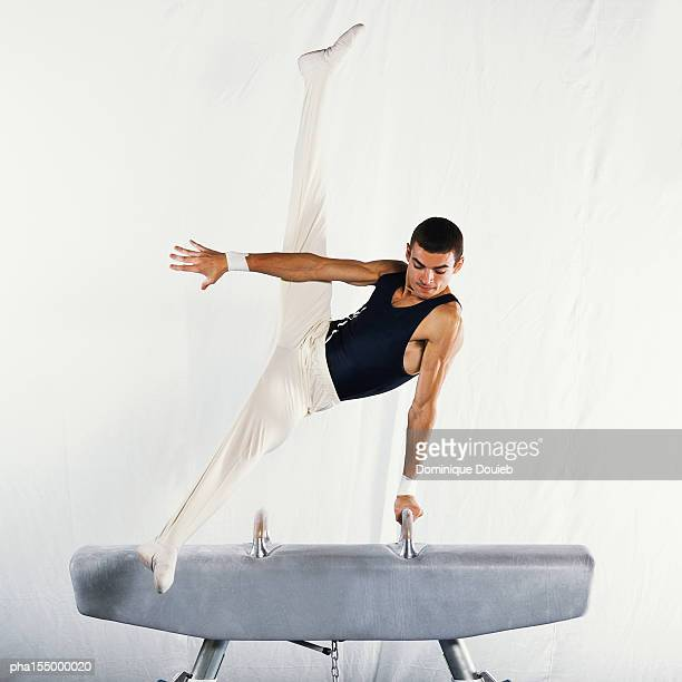 Young male gymnast performing scissors routine on pommel horse.