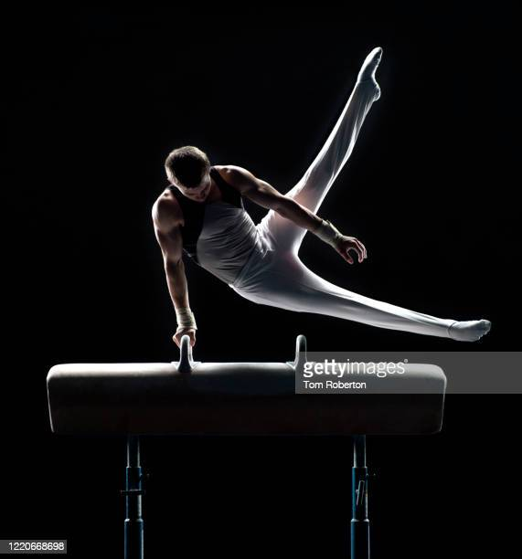 young male gymnast performing swing scissors on pommel horse - artistic gymnastics stock pictures, royalty-free photos & images