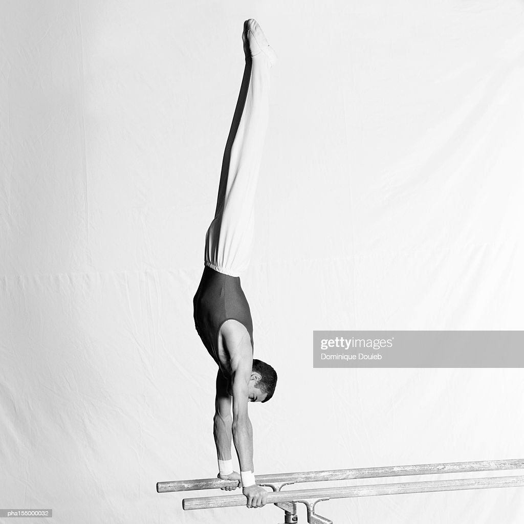 Young male gymnast upside down on parallel bars, side view. : Stockfoto