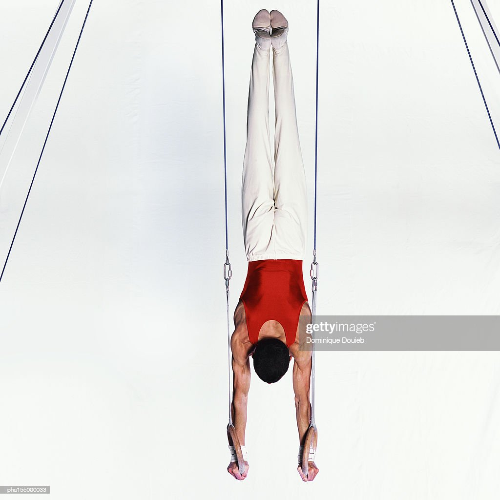 Young male gymnast upside down on rings, rear view. : Stockfoto