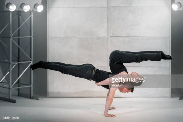 young male gymnasts shows muscular strength - black shirt stock pictures, royalty-free photos & images