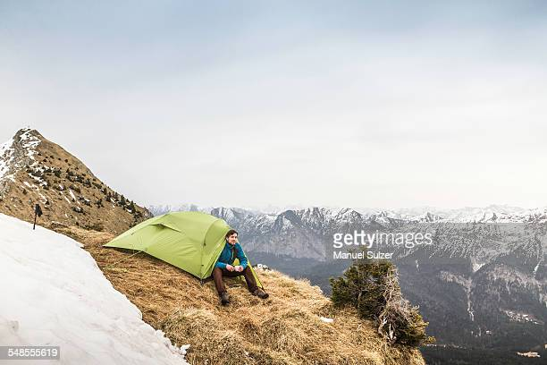 Young male hiker in front of tent on peak of Klammspitze mountain, Oberammergau, Bavaria, Germany