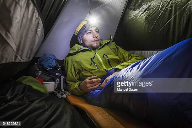 Young male hiker in tent on Klammspitze mountain, Oberammergau, Bavaria, Germany