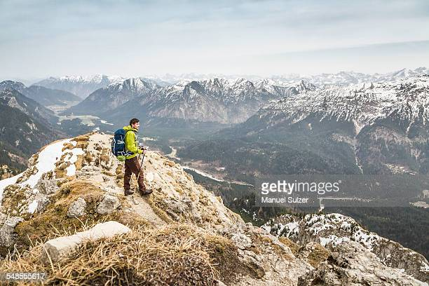 Young male hiker looking at view from Klammspitze mountain, Oberammergau, Bavaria, Germany