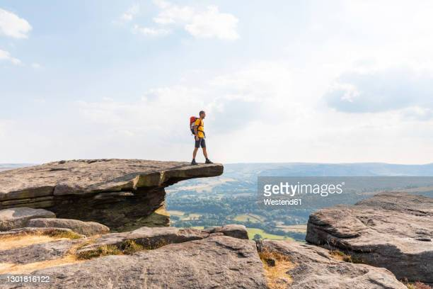 young male hiker looking at view while standing on top of mountain during sunny day - peak district national park stock pictures, royalty-free photos & images