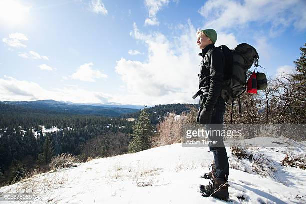 Young male hiker looking out from snow covered landscape, Ashland, Oregon, USA